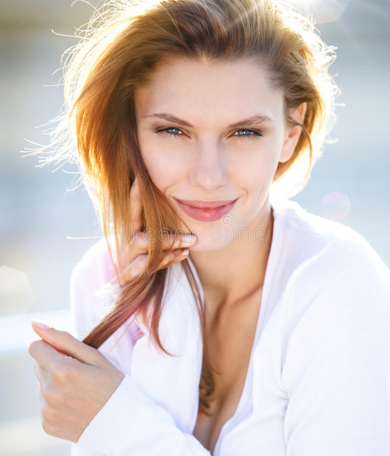 Delightful young woman holds her hair. Portrait of beautiful brunette smiling girl royalty free stock photos