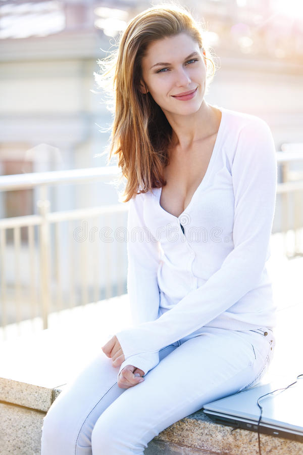 Delightful young woman just sitting. Smiling brunette girl in a light coloured clothing is sitting outdoors royalty free stock photography