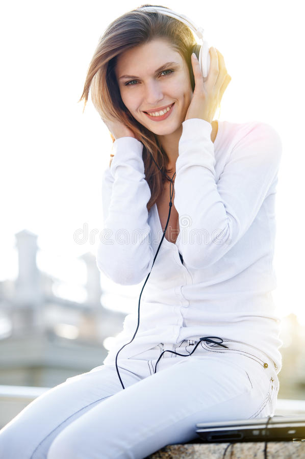Delightful young woman listening to music. Smiling brunette girl in a bright clothing listening to music on headphones royalty free stock photo