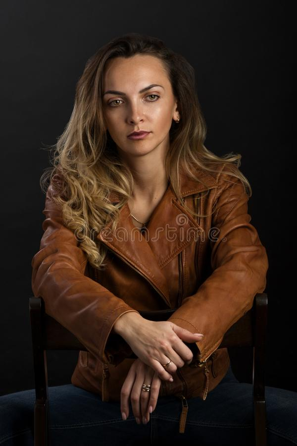 A delightful young woman with long blonde hair in a light brown leather jacket. Sits on a chair royalty free stock photos