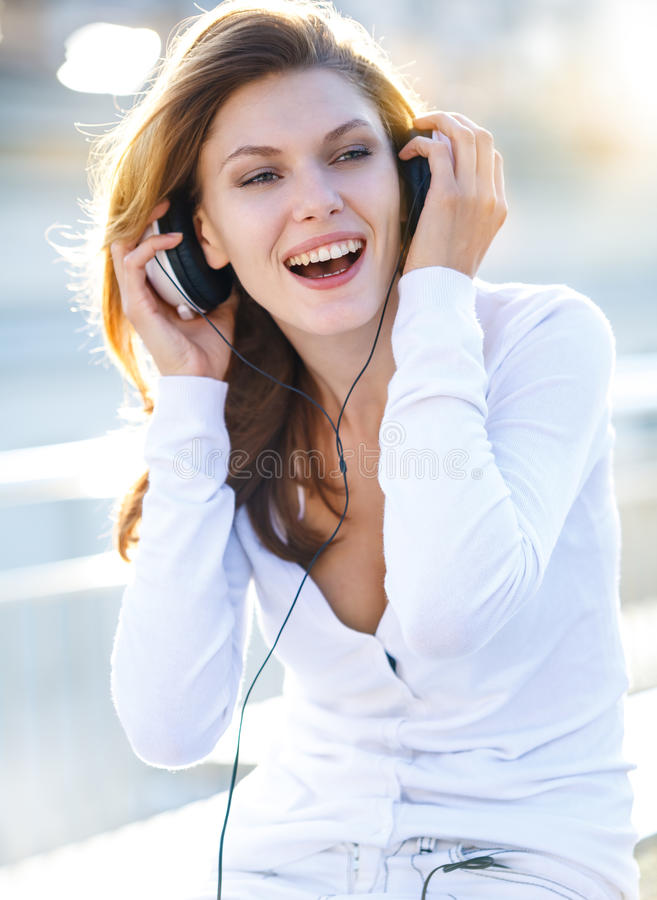 Delightful young woman taking her headphones off. Smiling brunette girl in a bright clothing looking to the side royalty free stock image