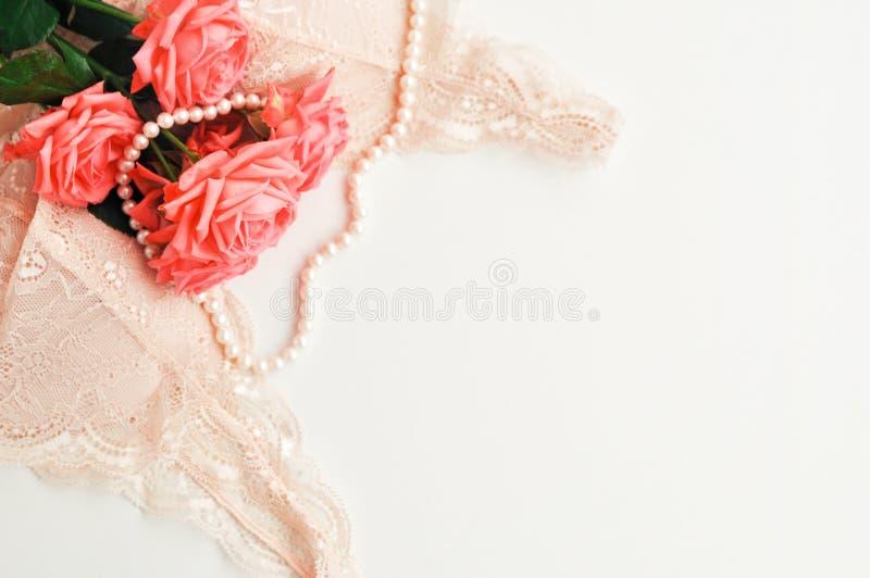 Delikat kvinnligt tema Rosa korallrosor tenderar färg på ett blekt - den rosa behå- och pärlahalsbandet på en vit bakgrund Top be royaltyfria foton