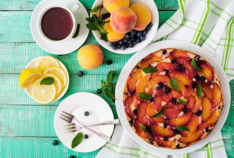 Delikat ljusbrun paj med persikor royaltyfri bild