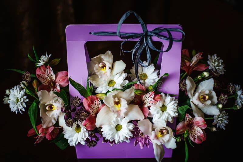 Delikat och härlig gåvabukett av blommor i en purpurfärgad cortonalkorg N?rbild Blommor royaltyfri bild