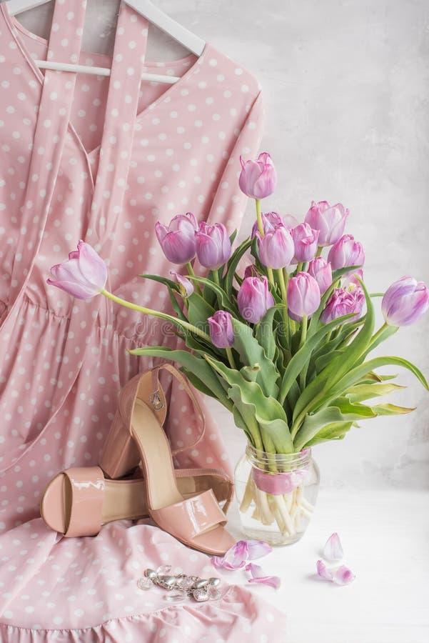 Delikat rosa prickklänning och beigea sandaler med en bukett av tulpan Kläder och skor i en försiktig stil V?r sommarlynne arkivfoton