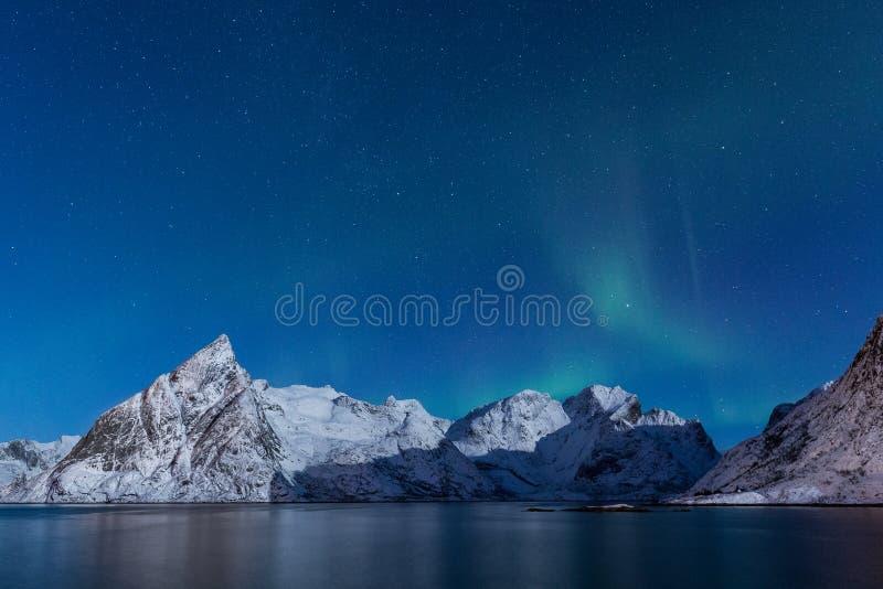 Delikata mjuka nordliga ljus över snöig berg i månsken royaltyfri bild