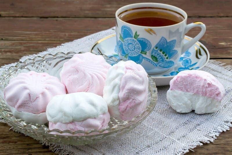 Delikata rosa och vita marshmallower och nytt te royaltyfria foton