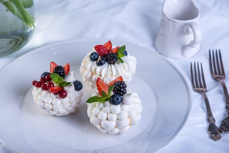 Delikata vita marängar med nya bär på plattan Efterrätt Pavlova Vit bakgrund bröllop för 8 pie arkivfoton