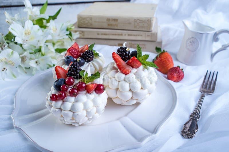Delikata vita marängar med nya bär på plattan EfterrättPavlova närbild En festlig bröllopstårta royaltyfria bilder