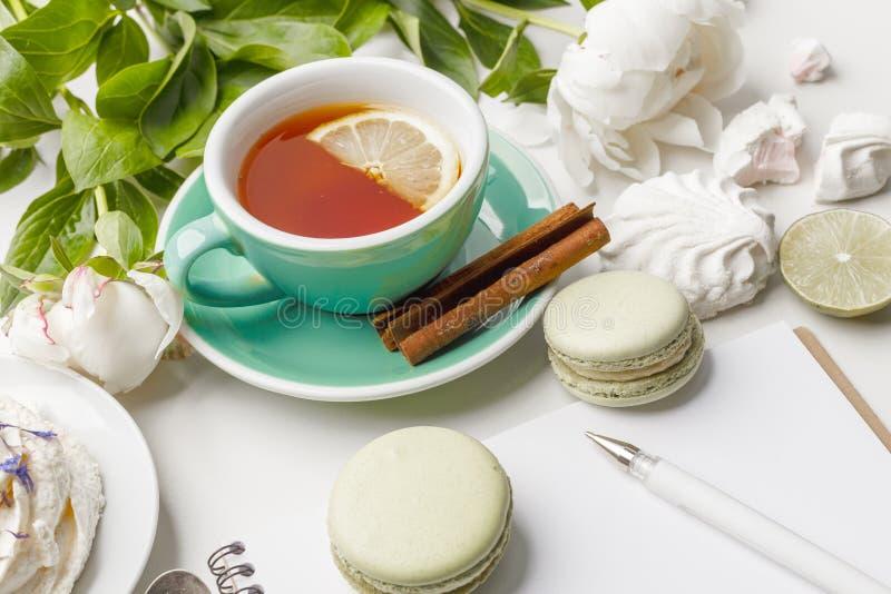 Delikata vita pioner med te, citronen, mogna jordgubbar och kakor på en vit tabell royaltyfri foto
