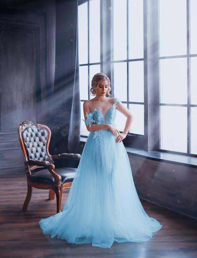 Delikatna, śnieżna królowa, stoi bezczynnie okno w bajecznie sukni z nagimi ramionami Pokój wypełnia z magicznymi promieniami obraz royalty free