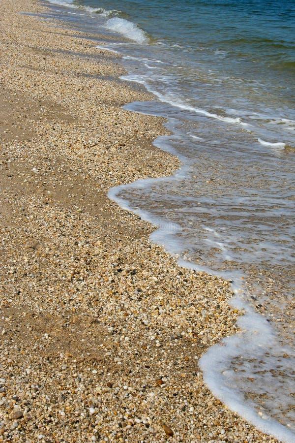 Delikatne fale owija na otoczaka piasku wyrzucać na brzeg obrazy stock