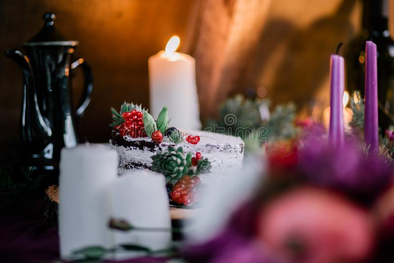 Delikatny ślubny biały tort dekorował z granatowem i sukulentem otaczającymi kwiatami i świeczkami fotografia stock