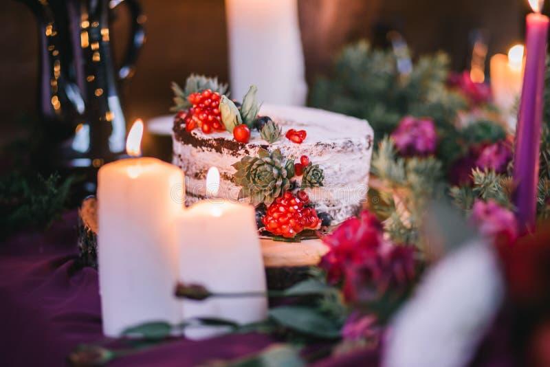 Delikatny ślubny biały tort dekorował z granatowem i sukulentem otaczającymi kwiatami i świeczkami obraz stock