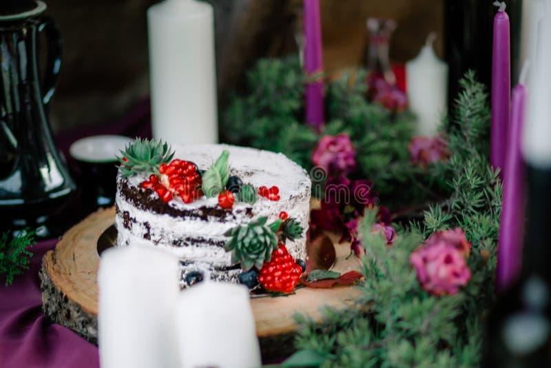 Delikatny ślubny biały tort dekorował z granatowem i sukulentem otaczającymi kwiatami i świeczkami zdjęcie stock