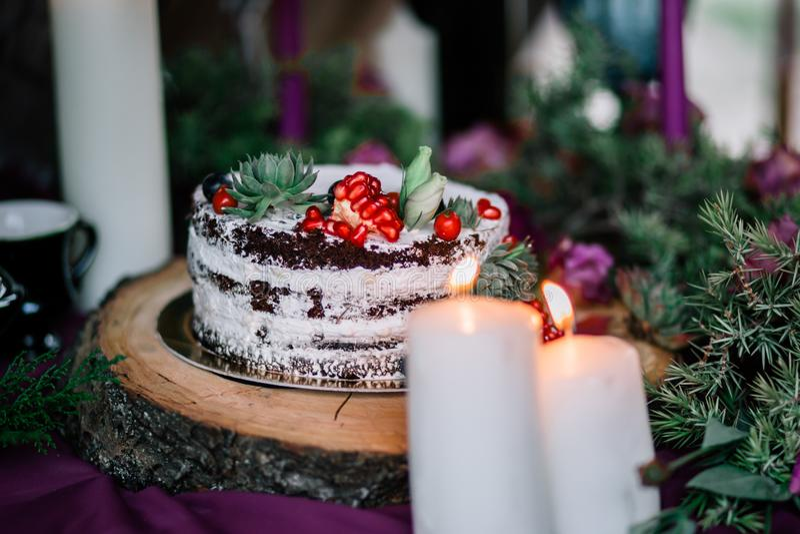 Delikatny ślubny biały tort dekorował z granatowem i sukulentem otaczającymi kwiatami i świeczkami fotografia royalty free