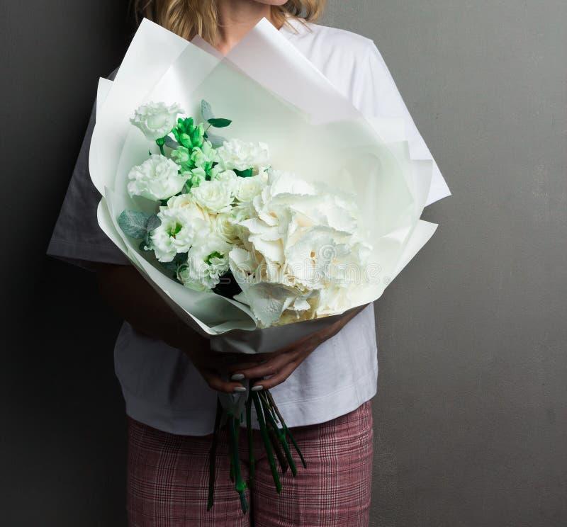 Delikatny bukiet zieleni i biali kwiaty, po?lubia bridal bukiet na szaro?ci ?cianie zdjęcia stock