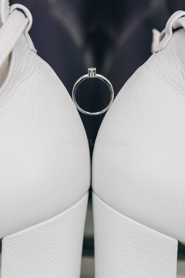 Delikatny Diamentowy pierścionek między Białymi butami zdjęcie stock