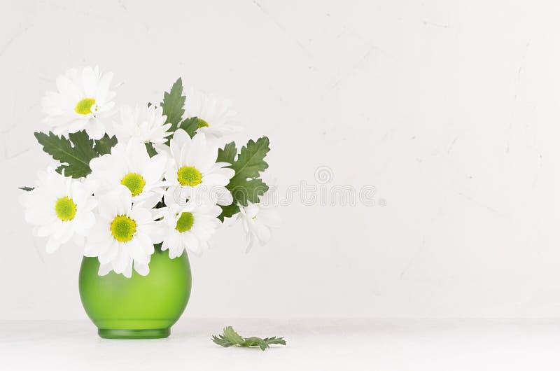 Delikatny domowy wystrój z świeżym ogrodowym latem kwitnie - chamomile w eleganckiej zielonego szkła wazie na białym drewno stole fotografia royalty free
