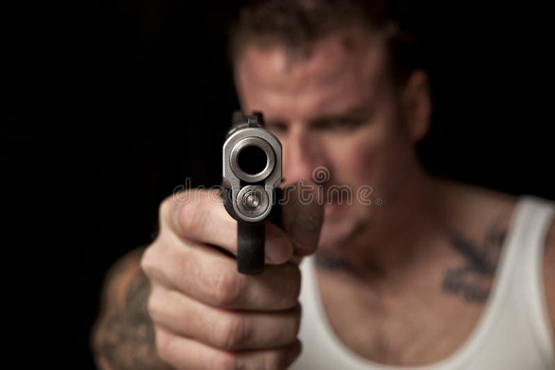Delinquente che indica una pistola fotografie stock
