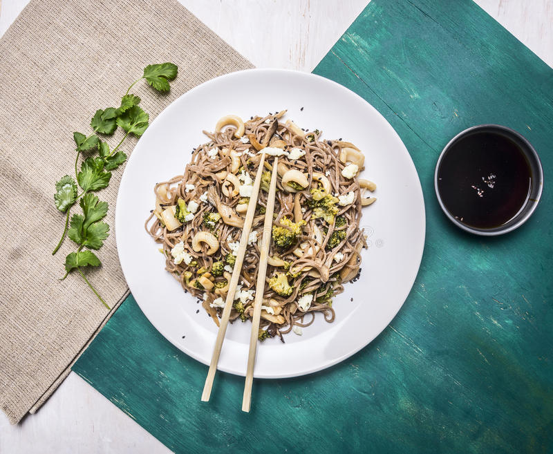 Delisious Japanese buckwheat noodles with squid and oyster mushrooms on a white plate with soy sauce chopsticks wooden rustic. Delisious Japanese buckwheat royalty free stock photo