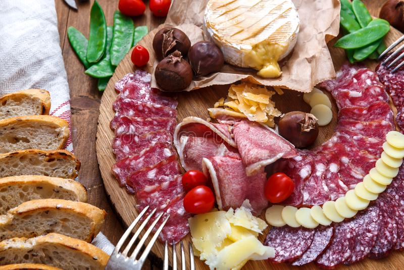 Delisious przekąski na drewnianej desce: kiełbasy, chleb, ser, kasztany i piwo, Zamknięty widok obraz stock
