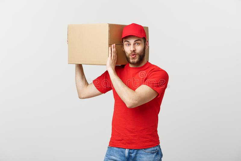Deliver Concept: Young caucasian handsome delivery man holding a box on shoulder. Isolated over grey background. royalty free stock photo
