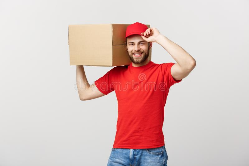 Deliver Concept: Young caucasian handsome delivery man holding a box on shoulder. Isolated over grey background. royalty free stock photography