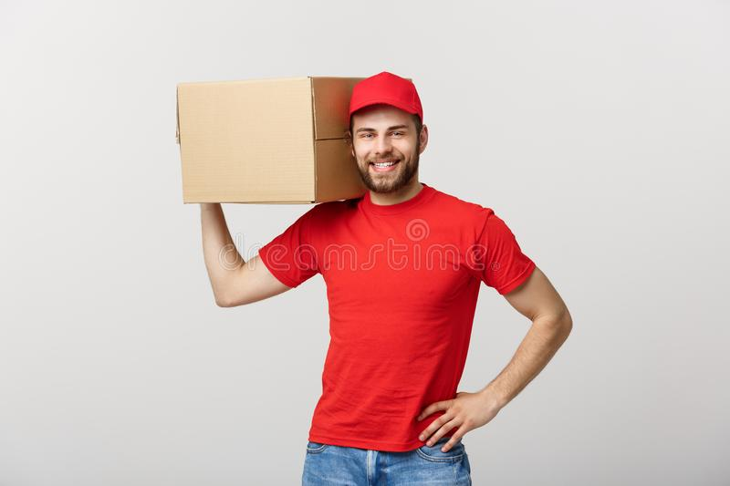 Deliver Concept: Young caucasian handsome delivery man holding a box on shoulder. over grey background. royalty free stock photography