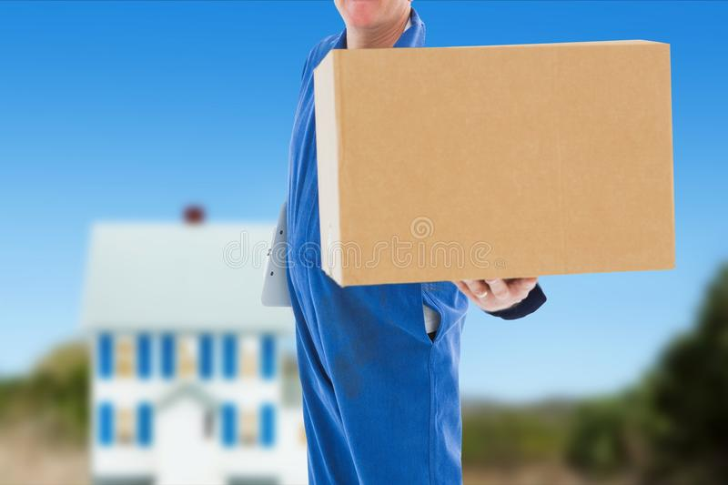 Deliver som bär en overall, rymmer en packe mot husbakgrund fotografering för bildbyråer
