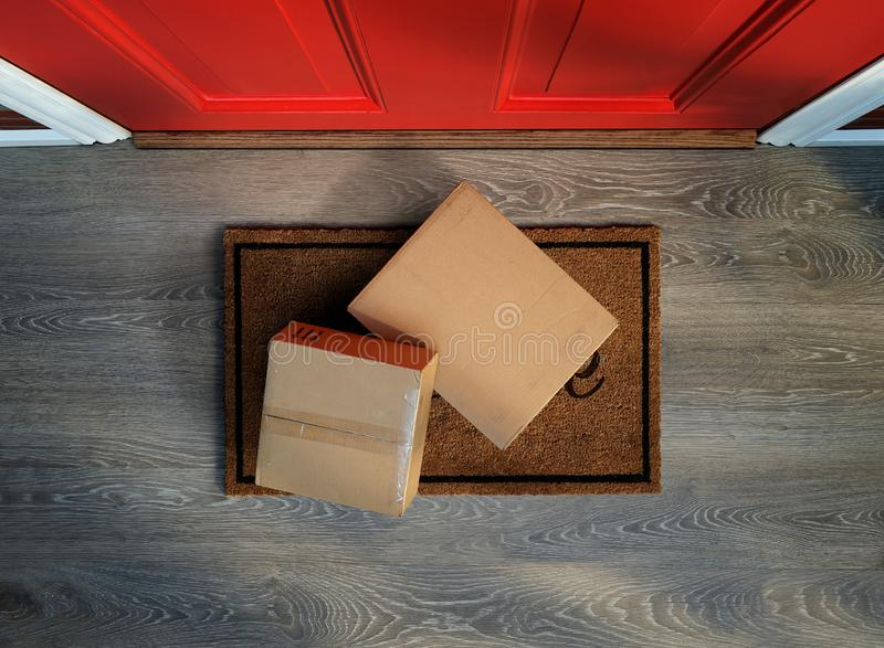 Delivered to the door, e-commerce purchases on welcome mat. Delivered to the door, boxes with e-commerce purchases on welcome mat. Add your own labels royalty free stock images