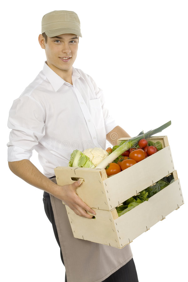Deliverer. Young man carrying two boxes of vegetables. Isolated on white in studio