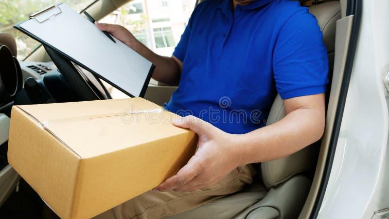 Deliverer che si siede in un furgone che tiene una scatola immagine stock