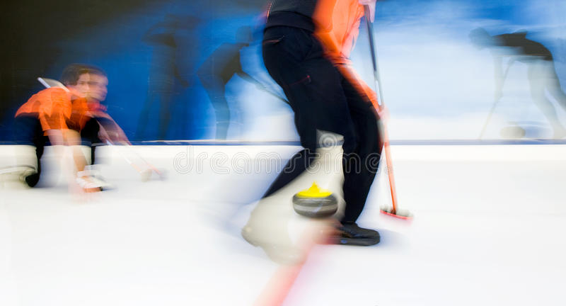 Delivering a curling stone. Two players of a curling team delivering a stone, brushing to adjust the precision and the curvature of the stone royalty free stock photo