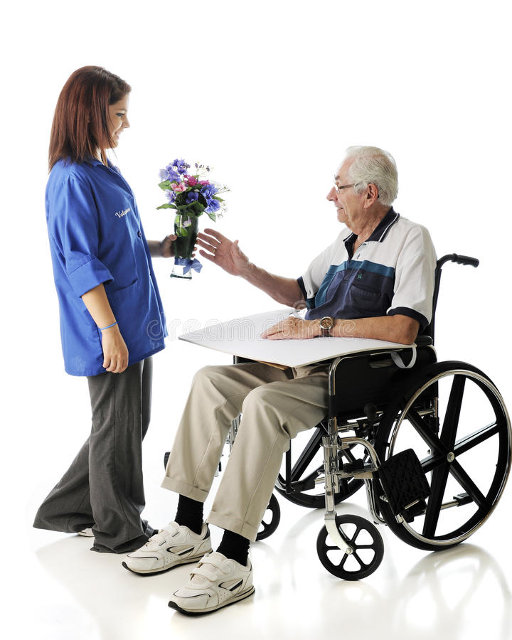 Delivering Flowers. An attractive teen volunteer delivering a vase of flowers to an elderly men in a wheelchair. On a white background stock photography