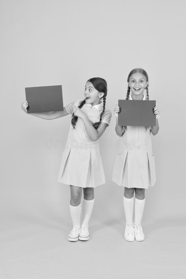 Delivering fresh information. Announcement and promotion. Schoolgirls cheerful pupils informing you. Girls school. Uniform hold posters. Back to school. School royalty free stock photo