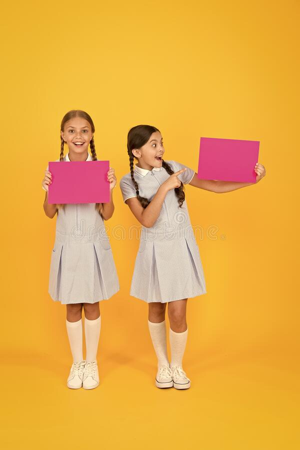 Delivering fresh information. Announcement and promotion. Schoolgirls cheerful pupils informing you. Girls school. Uniform hold posters. Back to school. School stock images