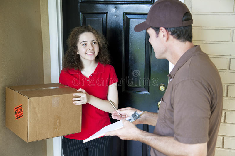 Delivering a Package. Delivery man brings a package to a customer's door and waits for a signature stock photos