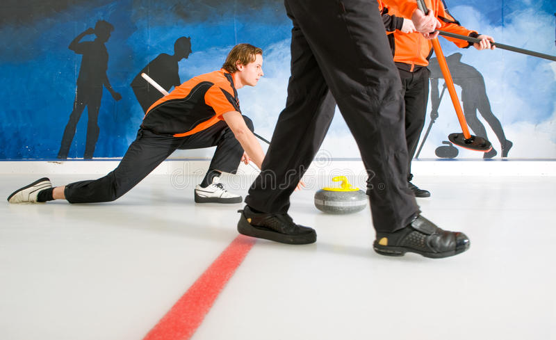 Delivering a stone. Curler, gliding on the ice, delivering a stone, with two sweepers, to act on the Skip's request royalty free stock photography