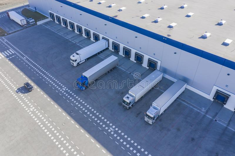 Delivering or Supply concept image. Trucks loading at facility. Logistics Center. Aerial View. Drone royalty free stock images