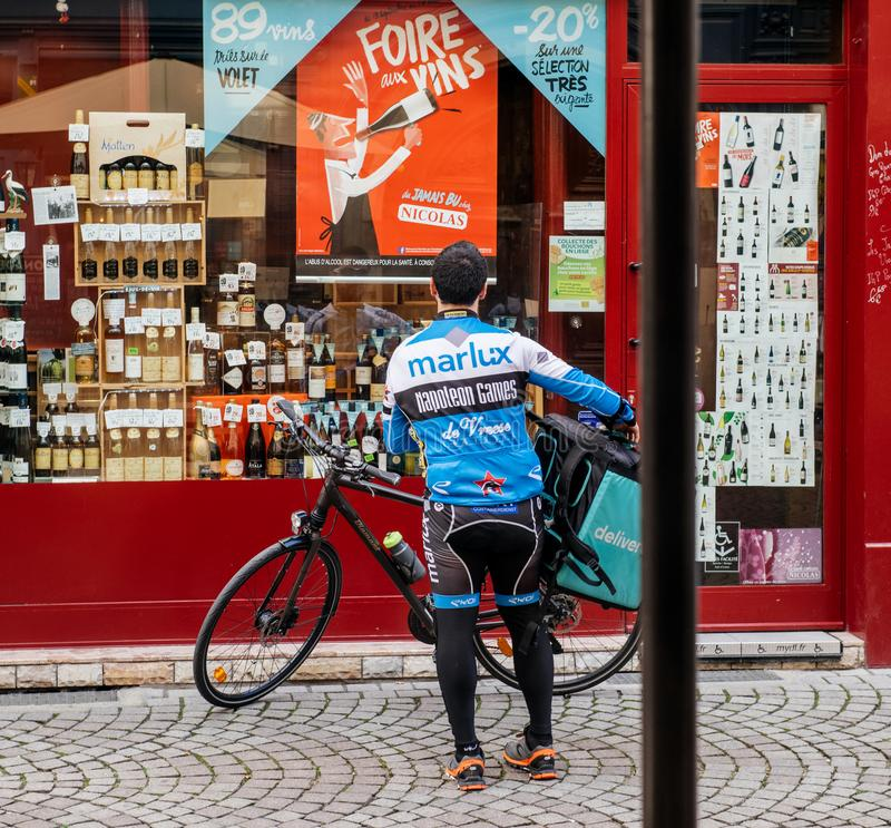 Deliveroo courier delivering food in modern city stock photos