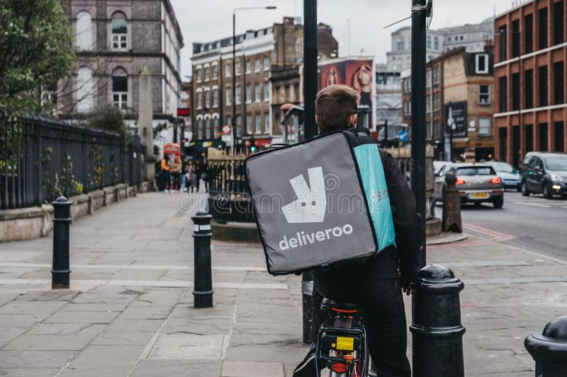 Deliveroo delivery driver on a street in East London, UK royalty free stock photos