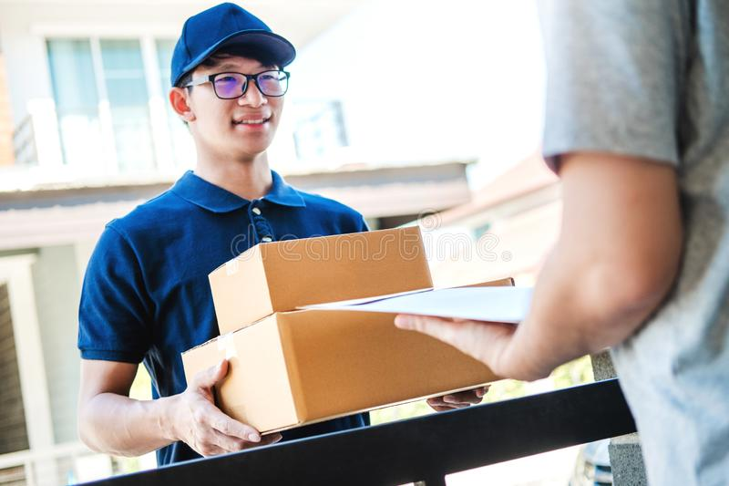 Delivery Asian man service with boxes in hands standing in front of Customer`s house doors stock images