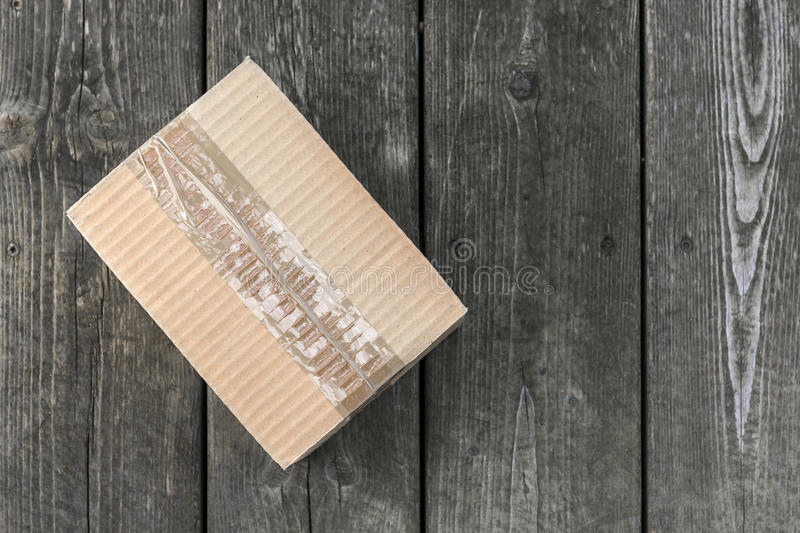 Delivery box. Cardboard delivery parcel box delivered to doorstep on old wood background, from above with copy space royalty free stock images