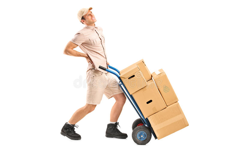 Delivery boy suffering from a back pain. Full length portrait of a delivery boy, suffering from a back pain, pushing a hand truck on white background royalty free stock photos