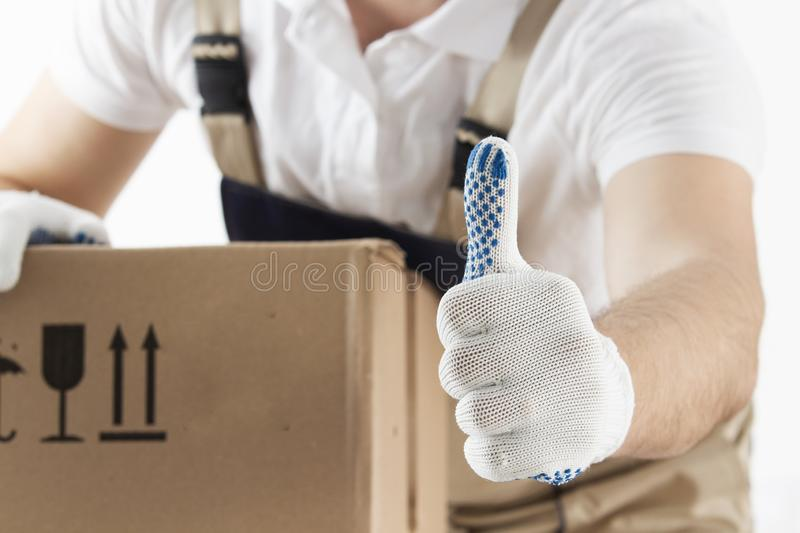 Delivery concept. Courier holds his thumb up. Man with cardboard box close-up. Relocation services. Loader with a box royalty free stock image