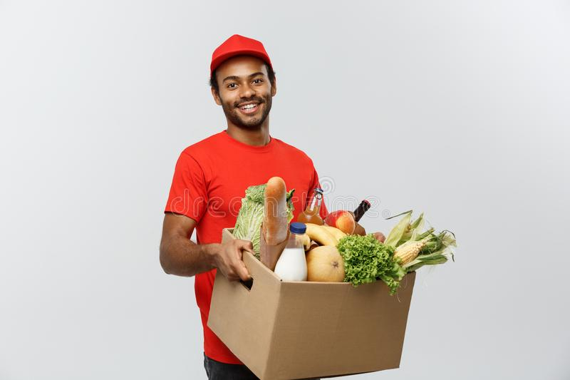 Delivery Concept - Handsome African American delivery man carrying package box of grocery food and drink from store. Isolated on Grey studio Background. Copy royalty free stock photography