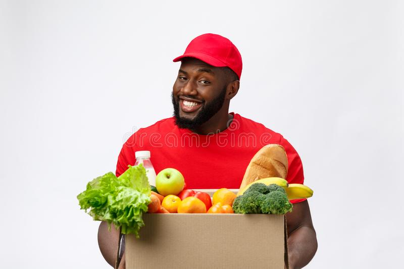 Delivery Concept - Handsome African American delivery man carrying package box of grocery food and drink from store. Isolated on Grey studio Background. Copy stock images