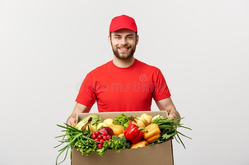 Delivery Concept - Handsome Cacasian delivery man carrying package box of grocery food and drink from store. Isolated on. Grey studio Background. Copy Space royalty free stock photography