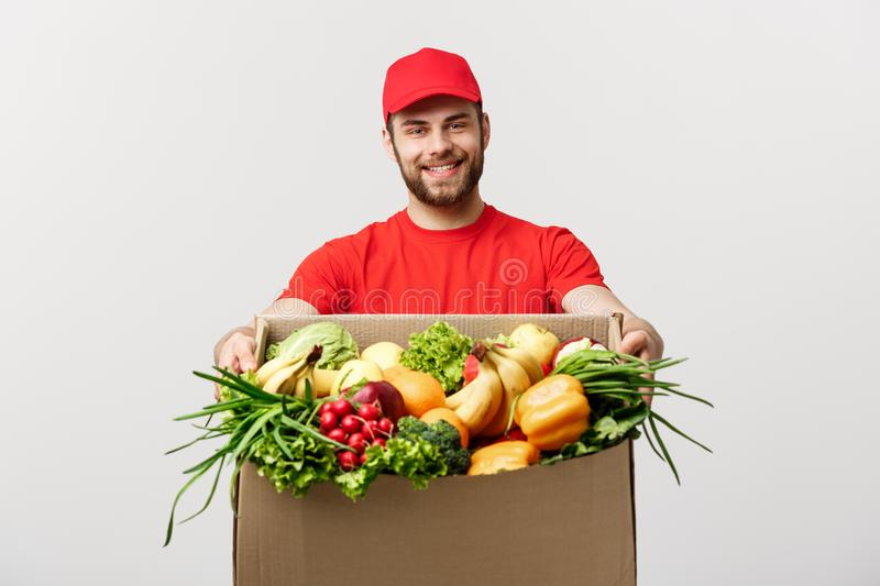 Delivery Concept - Handsome Cacasian delivery man carrying package box of grocery food and drink from store. Isolated on. Grey studio Background. Copy Space royalty free stock photo